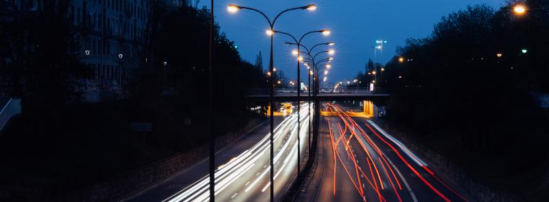 Wieczorne zdjęcie zaświeconych latarni drogowych przedzielających pasy jezdni w dwóch kierunkach