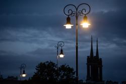 Zaświecone latarnie wieczorem, w tle wieże kościoła