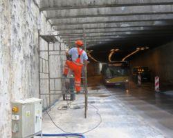 Robotnik wspinający się na rusztowanie pod mostem.
